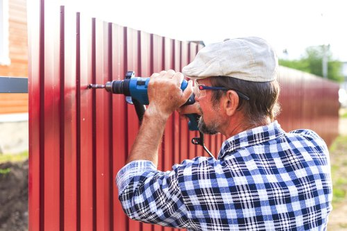 A professional repairing the fence