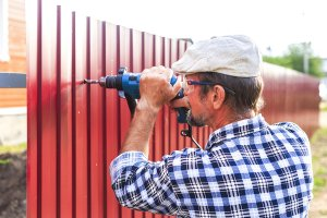 Man installing red privacy fence in Palm Beach